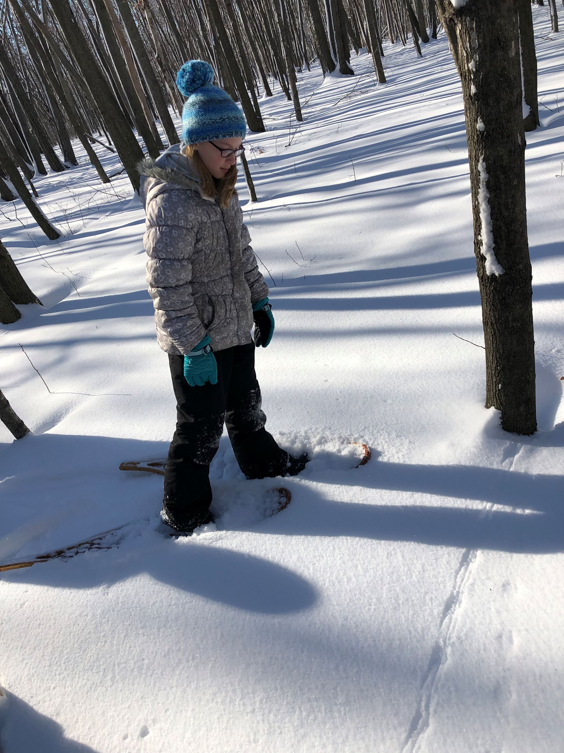 a girl on snowshoes looking at animal tracks in the snow