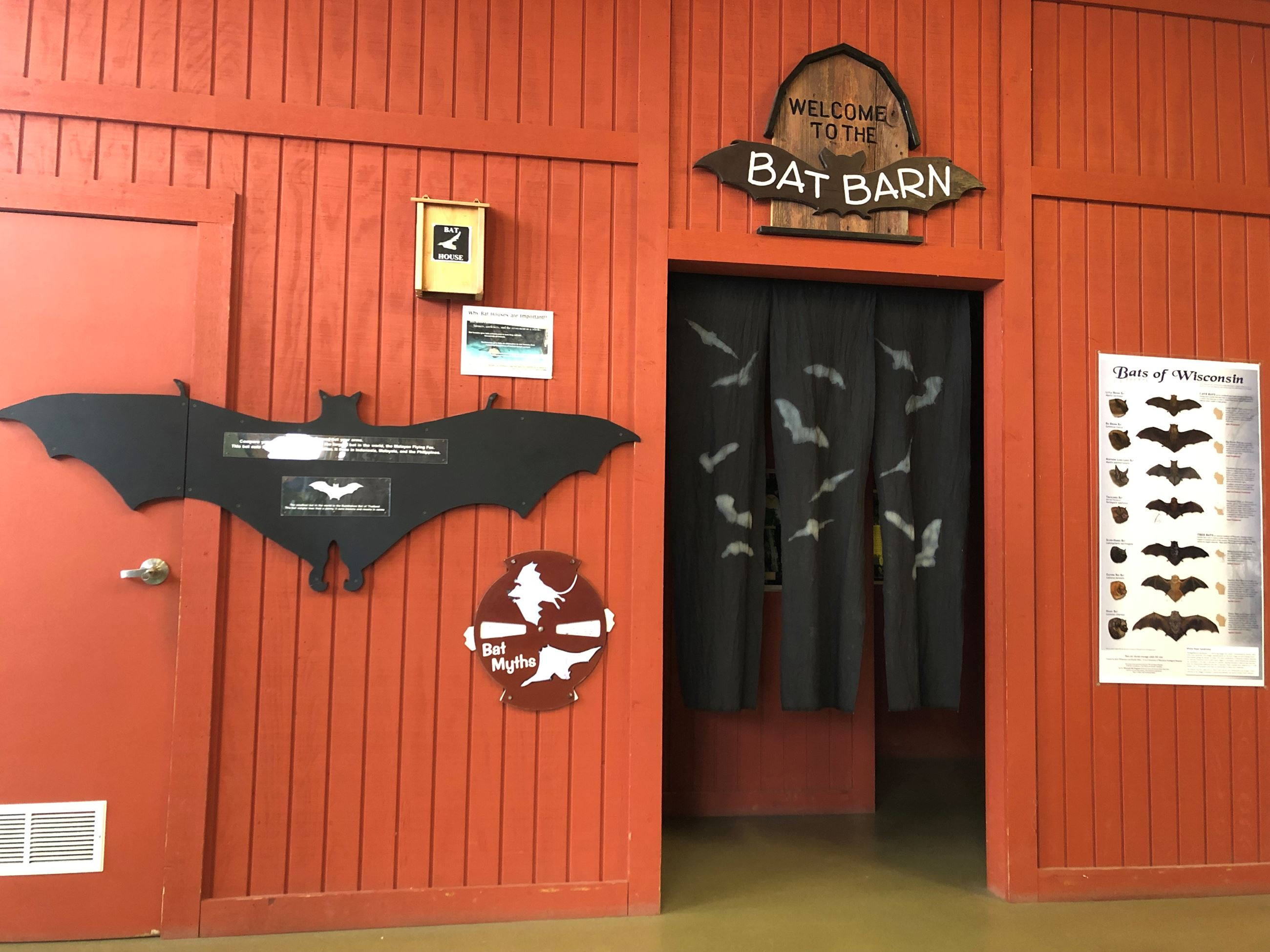 A red wooden wall that has a sign that says Bat barn on it. There is a large black cutout of a bat o