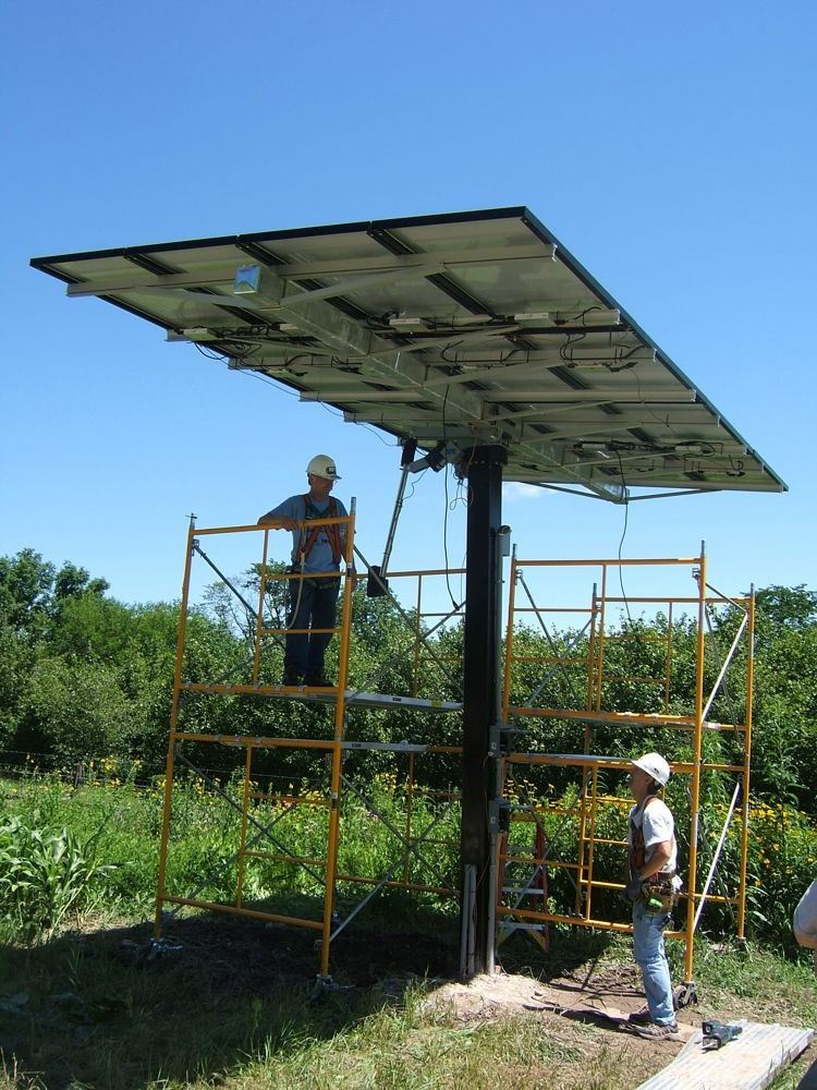 Two men standing under a solar panel looking up. One man is on the ground and the other is on yellow