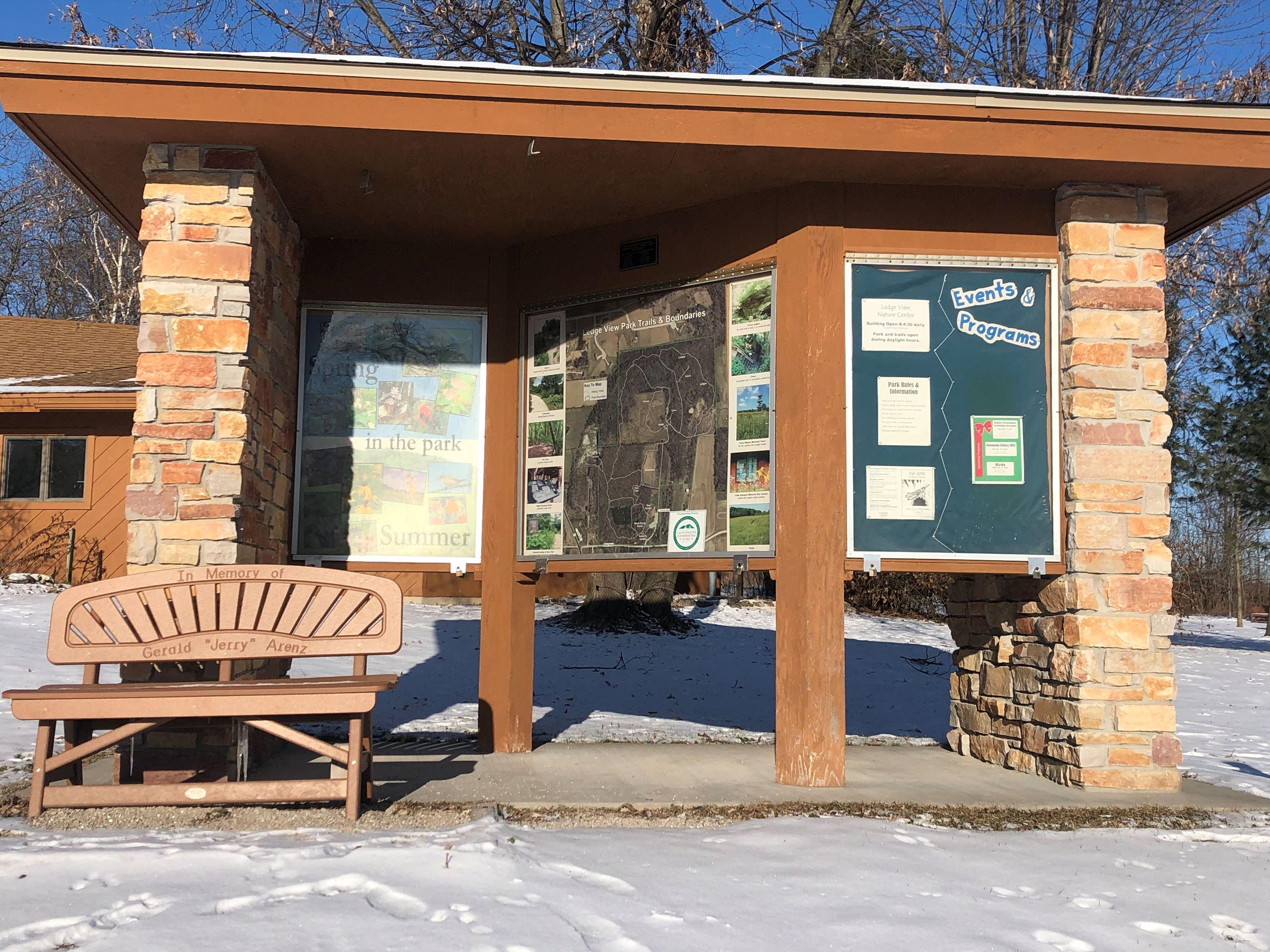 A stone and wood kiosk with information on it for park visitors.