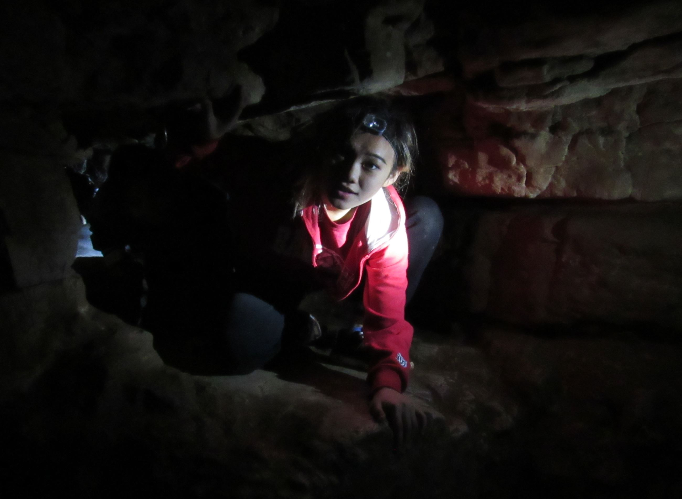 A teenage girl wearing a red sweatshirt and a headlamp crawling through a tunnel in a cave.